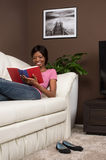 Beautiful youthful woman relaxing at home on couch. Young woman on sofa reading novel Stock Photo