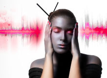 Feeling the Energy of Music. Good Vibrations. Beautiful zen woman with creative high fashion makeup. Painted silver with hands on the sides of the face and eyes Royalty Free Stock Image