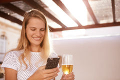 Beautifull blond with beer and cellphone Stock Photo