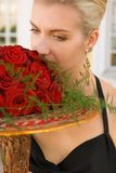 Beautifull blond girl. Beautiful blond girl with a bouquet of red roses Stock Image