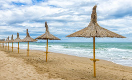 Beautifull empty beach in a windy day with straw umbrellas Stock Photos