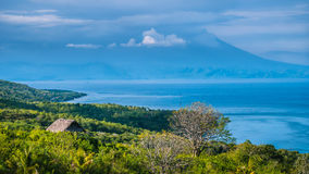 Beautifull evening view to St. Agung Vulcano on Bali from Nusa Penida Island. Partly Covered by Clouds. Indonesia Stock Photos