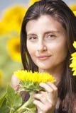 Beautifull flicka i ett solrosfält Arkivfoton