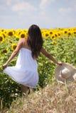 Beautifull flicka som leker nära solrosfält Arkivbild