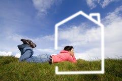 Beautifull Frau im Gras, das mit neuem Haus träumt Lizenzfreies Stockfoto