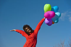 Beautifull girl with few balloons in the form of a heart. Girl with a bunch of balloons in the form of heart on the background of the sky Stock Photography