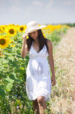 Beautifull girl walking in a cropland. Near a sunflower field with a hat royalty free stock photography