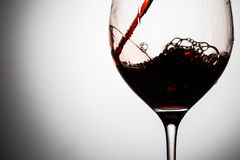 In beautifull glass poured red wine with waves and splashes Stock Photography