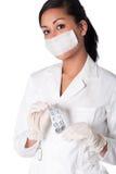 Beautifull Indonesian nurse with cap and pills. Beautiful Indonesian nurse in white uniform Royalty Free Stock Photo