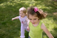Beautifull little sisters running on the park Stock Images