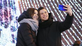 Beautifull man and woman makes a selfie on phone, smiling in New Year`s Night stock video