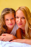Beautifull mom and daughter. Happy mother and daughter laying in bed ( yellow background Royalty Free Stock Photo