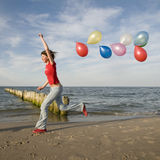 Beautifull teenage girl on the beach. Teenage girl playing with balloons on the beach stock photo