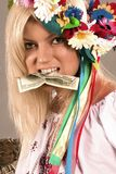 Beautifull ukrainian girl with dollar in her teeth. Beautifull ukrainian girl in traditional clothes with dollar in her teeth Royalty Free Stock Photos
