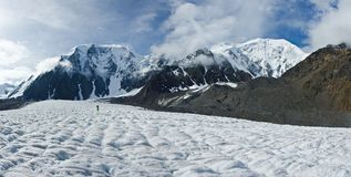 Panorama of valley with view to snow mountains and alpinist. Beautifull valley with view to snow mountains in Altaj, Russia at the summer royalty free stock image