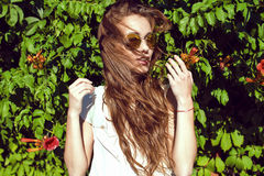 Beautifull woman with long chestnut hair blown by the wind in mirrored sunglasses standing at the creeper hedge Royalty Free Stock Image