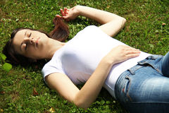 Beautifull woman is lying and resting in the grass. Photo of the Beautifull woman is lying and resting in the grass Royalty Free Stock Image
