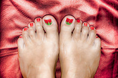 Beautifull woman's feet on a red satin sheet Stock Photo