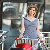 Beautifull woman with shopping cart. Beautifull blond with shopping cart near supermarket royalty free stock image