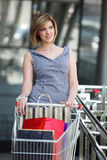 Beautifull woman with shopping cart. Near stock photography