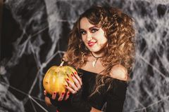 Beautifull woman in a witch`s costume is holding pumpkin in front of black wall with spider net royalty free stock image