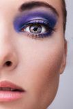 Beautifull young blond model with blue make-up. Close-up eyes. Natural health beauty of a woman face royalty free stock photography