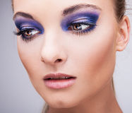 Beautifull young blond model with blue make-up. Close-up eyes. Natural health beauty of a woman face stock image