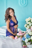 Beautifull young brunette pregnant woman in awesome purple dress close to blue sofa and cute flowers. Stock Photo
