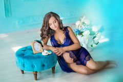 Beautifull young brunette pregnant woman in awesome purple dress close to blue sofa and cute flowers. Royalty Free Stock Photos
