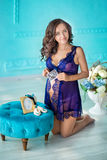 Beautifull young brunette pregnant woman in awesome purple dress close to blue sofa and cute flowers. Stock Photos