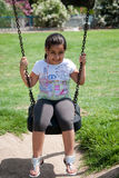 Beautifull young girl playing on the swings. A cute little girl playing on the swings on a sunny day Royalty Free Stock Photography