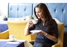 Beautifull young woman drinking cofee in restaurant. Portrait of beautifull young woman drinking cofee. Looking at cofee cup Stock Photo