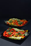 Beautifully and appetizingly cut fresh vegetables and cabbage of broccoli on two black ceramic plates. Beautifully and appetizingly cut fresh vegetables and Stock Photo
