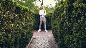 Among the beautifully cropped bushes in the park, a young man in a white shirt, trousers, stylish suspenders and bow tie. Stands and smiles a little stock footage