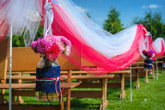 Beautifully decorated benches for wedding ceremony on the lawn Royalty Free Stock Image