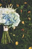 Beautifully decorated bride`s bouquet of different bright colors and green leaves lies on the autumn grass. Wedding theme royalty free stock photos