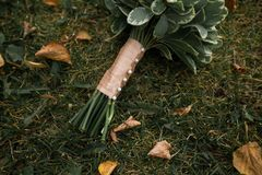 Beautifully decorated bride`s bouquet of white roses and green leaves lies on the autumn grass. Wedding theme stock image
