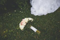 Beautifully decorated bride`s bouquet of white roses, peonies and green leaves lies on the green grass. Near the hem of the bride. `s dress. Wedding theme stock photography