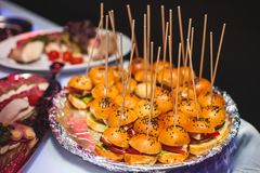 Beautifully decorated catering banquet table with different hamburgers burgers sandwiches on a plate on corporate christmas birthd. Beautifully decorated Royalty Free Stock Images