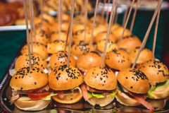 Beautifully decorated catering banquet table with different hamburgers burgers sandwiches on a plate on corporate christmas birthd Stock Photography