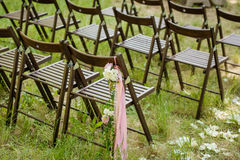 Beautifully decorated chairs for wedding reception outdoors. Stock Photo
