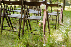 Beautifully decorated chairs for wedding reception outdoors. Royalty Free Stock Photography