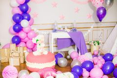 Beautifully decorated children`s party with balloons flowers and sweets. A lovely delicious candy bar in pink and purple colors for a little princess on her 1st Royalty Free Stock Photo