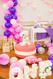 Beautifully decorated children`s party with balloons flowers and sweets. A lovely delicious candy bar in pink and purple colors for a little princess on her 1st Royalty Free Stock Photos