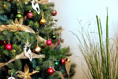 Beautifully decorated christmas tree with red gold and green bau. Bles and decorations, with bamboo plant Stock Photo