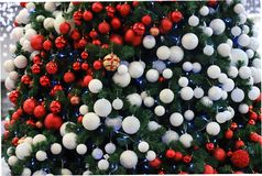 A beautifully decorated Christmas tree with red, white balls and garlands. Design and scenery, New Year s concept, winter holiday. Magic atmosphere stock photography