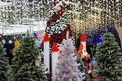 A beautifully decorated Christmas trees with red, white balls and garlands. Design and scenery, New Year s concept, winter holiday. Christmas shopping mall royalty free stock photo