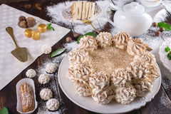 Beautifully decorated dessert table where the cake with meringue on a dark wooden table. Arrangement of delicious sweets. Beautifully decorated dessert table stock photography