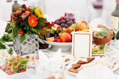 Beautifully decorated festive table with meal in center of which stands vase with bouquet of flowers, plate of fruit. Beautifully decorated festive table with a Royalty Free Stock Photography