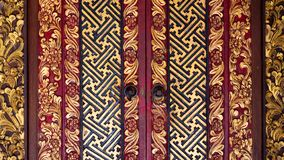 Beautifully decorated Indonesian wooden door in black red and gold royalty free stock image